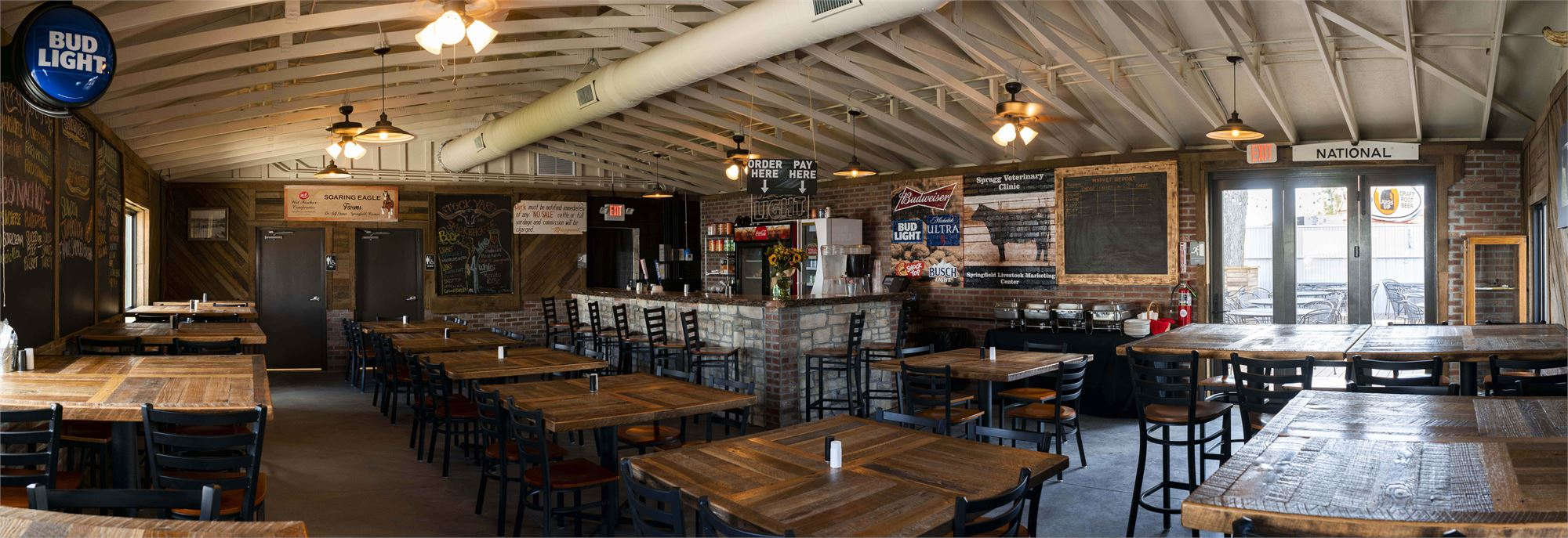 Inside Stockyard Smokehouse. Several wood tables are set up with memorabilia on the walls from the old Stockyards. The ceilings are white with wood walls and chalkboards.