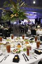 Banquet set up with over 150 tables and large flower center pieces. In the background is a large screen and stage