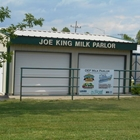 Entrance to Joe King Milk Parlor, a tan building with green trim and two large white roll up doors