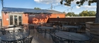 Patio of the Stockyard Smokehouse with black wire tables and chairs. There is a tree shading the outside seating.