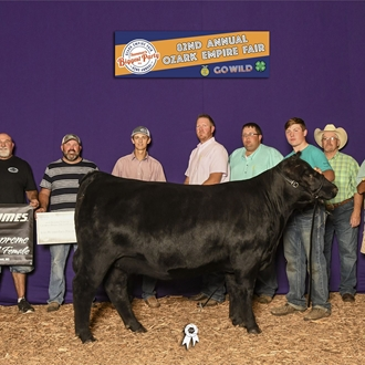 Exhibitor and family proudly pose with their reserved bred and owned cattle.