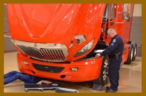 Technician working on an orange big rig truck.