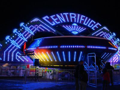 Centrifuge ride at night with several blue lights