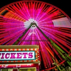 View of the ticket booth in front of the lit up Ferris wheel
