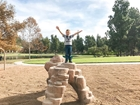 Boy standing on rocks at Ralph B Clark Park in Buena Park, CA