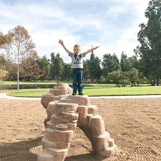 Little boy on rocks at Ralph B Clark Park in Buena Park, CA