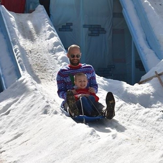Father and son on a sled on snow at Candy Caneland in Buena Park
