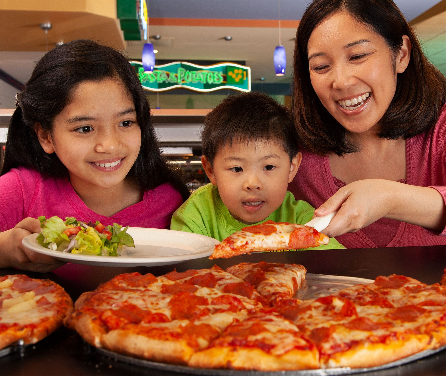 Family at Buffet with pizza and salad at John's Incredible Pizza in Buena Park, CA