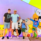 Two dad and two sons in front of a mural at The Source OC in Buena Park