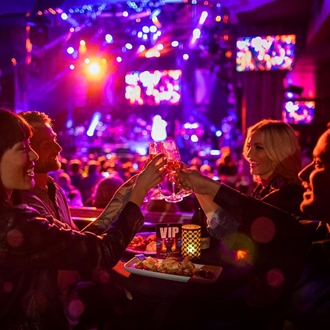 Concert attendees at a VIP table with a concert in the background at the House of Blues Anaheim