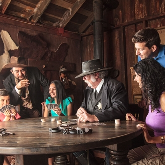 Sheriff and cowboy playing cards with a family at Ghost Town Alive! at Knott's Berry Farm in Buena Park