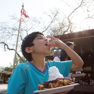 Boy eating funnel cake at Knott's Berry Farm in Buena Park, CA.