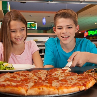 Boy and girl eating pizza at  John's Incredible Pizza in Buena Park, CA