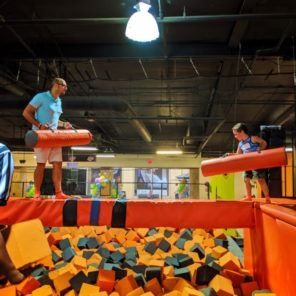 Family on beam at Big Air Trampoline Park in Buena Park, CA.