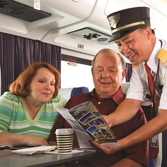 Train Conductor showing couple a brochure on an Amtrak train