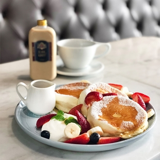 Plate of souffle pancakes with fruit with a cup of coffee at Basilur Tea & Coffee