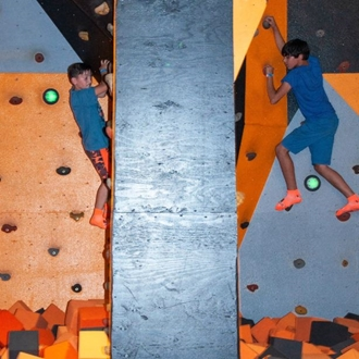 Two children playing on rock climbing wall at Big Air in Buena Park