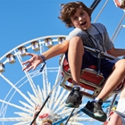 Boy on a swing with a Ferris wheel in the background at the OC Fair & Event Center