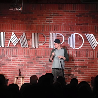 Pete Davidson with a sign in the background that says improv at the Brea Improv