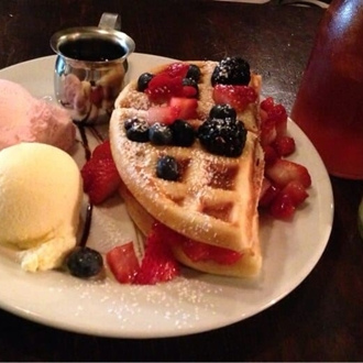 Waffles, ice cream, and syrup on a plate at Cafe 7th Home in Buena Park