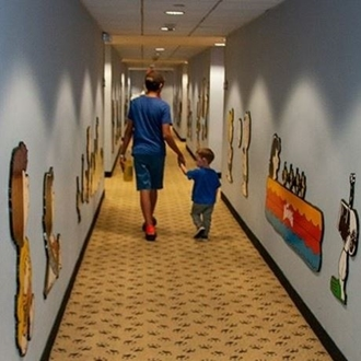 Father and son walking down snoopy hallway at Knott's Berry Farm in Buena Park