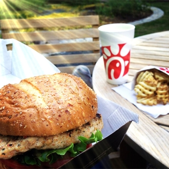 Chicken sandwich, Chick-Fil-A cup, and fries on a park table with a bench in the background