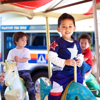Children on a carousel at the Children's Museum at La Habra