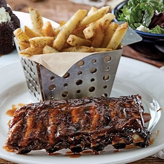 Ribs and fries on a plate with a chocolate cake and salad in the background at Chili's in Buena Park