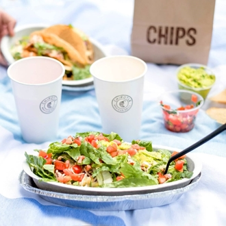 Two burrito bowls, two cups, and a chips bag in the background at Chipotle