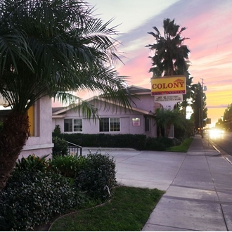Exterior of The Colony Inn at sunset in Buena Park