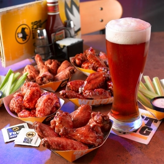 Wings, celery, and beer in front of a Buffalo Wild Wings menu at Buffalo Wild Wings in Buena Park