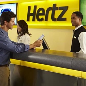 Guest at the service desk speaking with an employee at Hertz Car Rental in  Buena Park