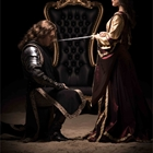 Black knight on one knee in front of queen with sword at Medieval Times in Buena Park
