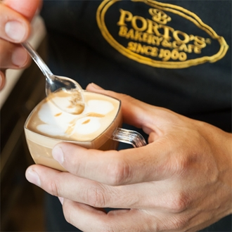 Man holding coffee with spoon at Portos in Buena Park, CA