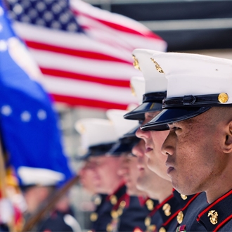 Marines with a flag behind them