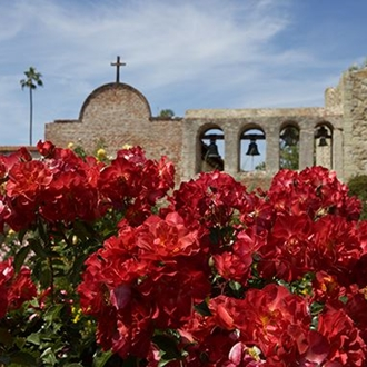 Exterior of Mission San Juan Capistrano with flowers in the foreground