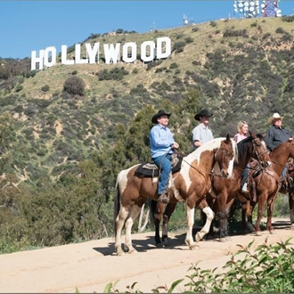 Horse back riders with the Hollywood sign in the background at Sunset Ranch Horseback Riding
