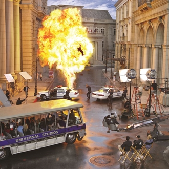 Stunt explosion with fire in front of camera crew and a tour bus at Universal Studios Hollywood