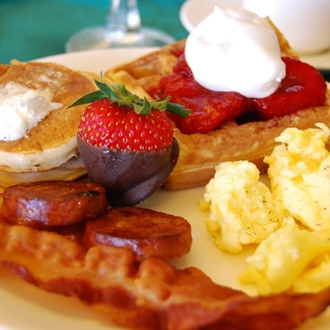 Pancakes, eggs, bacon, waffles, and chocolate covered strawberries on a plate at Ventanas Restaurant at the Holiday Inn in Buena Park