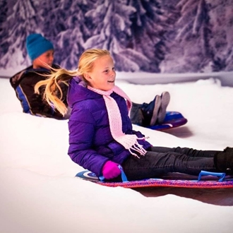 Boy and girl on sled and snow at Winterfest OC