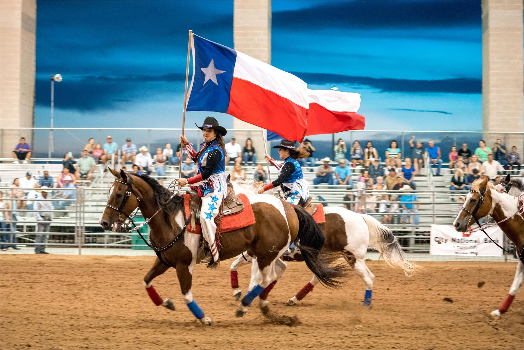 Cowgirls riding through the arena with Texas Flag