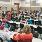 Long rows of seating with tables during a fundraiser event in the Indoor Expo Hall.