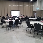 Confrence style setup with round tables and projector in the South End of the Indoor Expo Hall