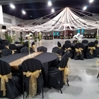 chairs and tables decorated with black table fabric with a metal tent decorated in white tool and christmas lights