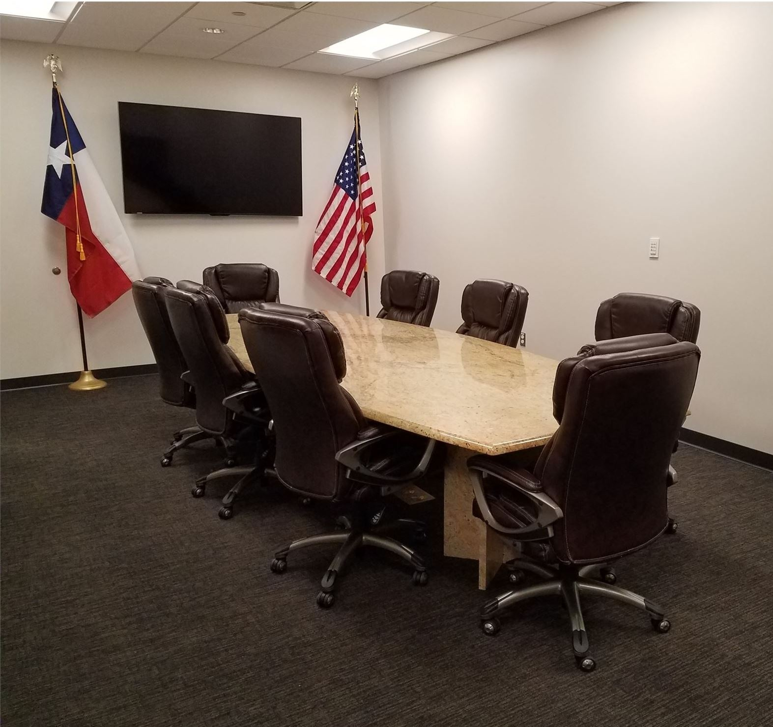 Empty Confrence room with large table and eight office chairs around the table