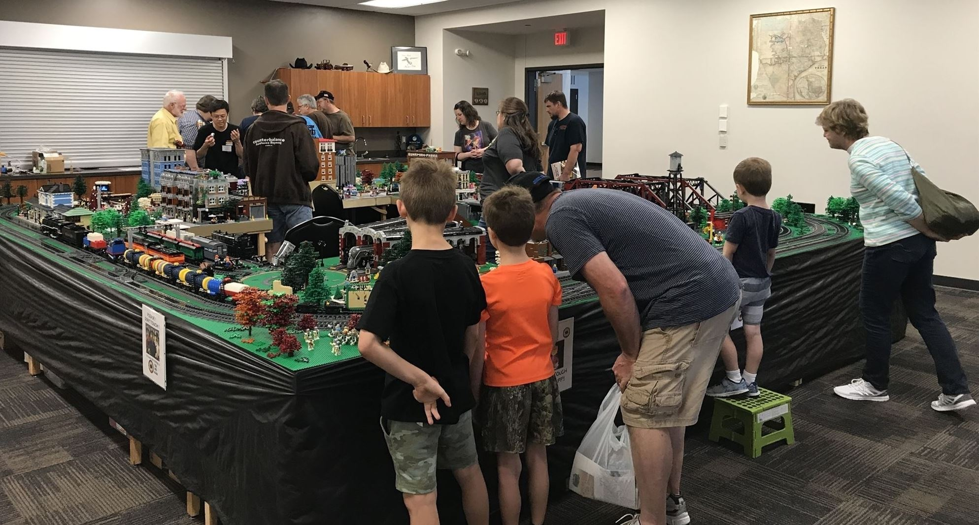 Families around the lego model train exhibit in the meeting room