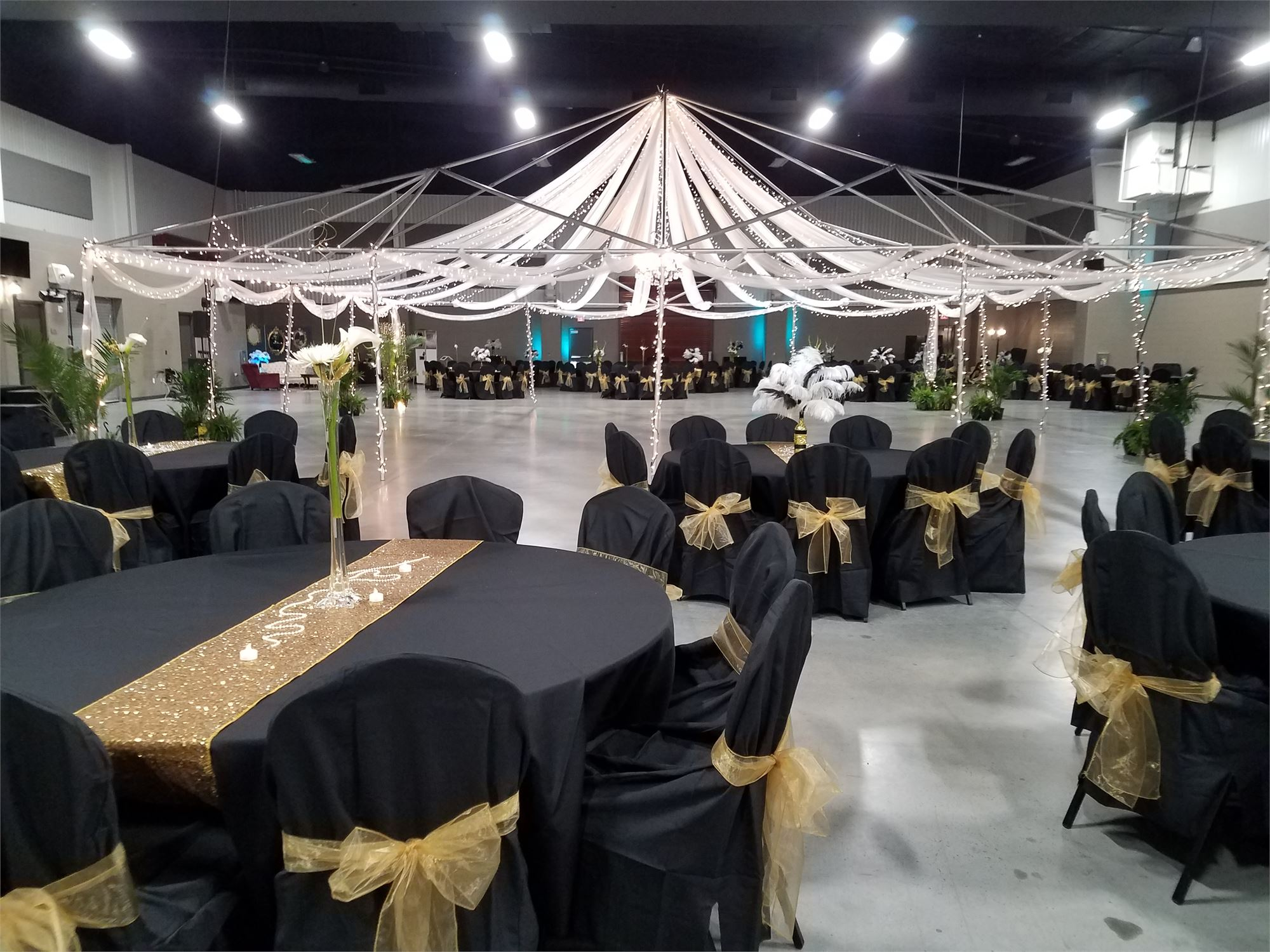Indoor Expo Hall decorated for the Taylor Prom. Tables covered in black table clothes and a canopy with lights over the dance floor