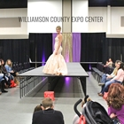 Runway show for a wedding expo. Lady wearing a white floor length mermaid style gown
