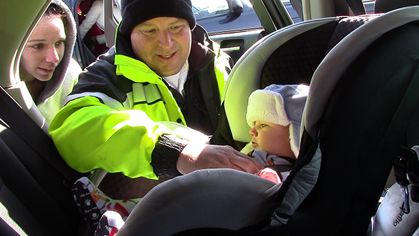 EMS and parent helping buckle a child in a carseat