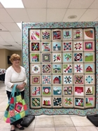 Nancy Straight stands with the 2019 Quilt Block Challenge Quilt that she won during the raffle held Saturday, August 10th.